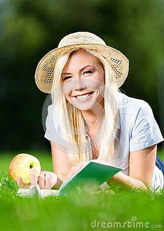 Free Girl In Straw Hat With Apple Reads Book On The Grass Royalty Free Stock Photo - 33916255