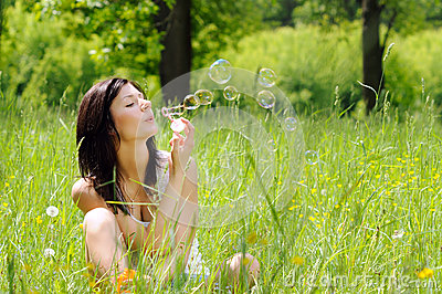 Girl inflating soap bubbles