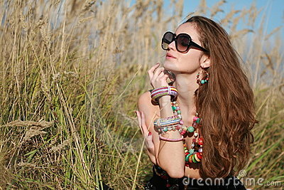 Girl with jewelry and glasses sits in grass field