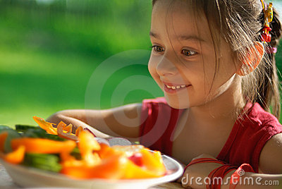 The girl joyfully is surprised to tasty vegetables