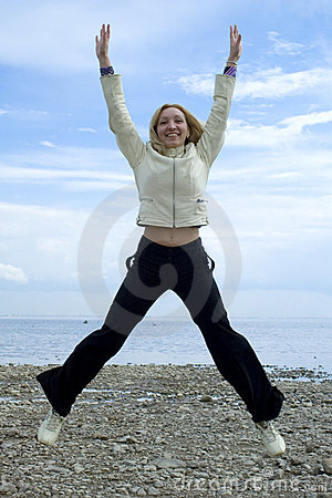 Girl jumping beside Baltic sea