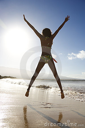 Girl jumping on beach.