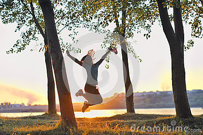 Girl jumping over sunset