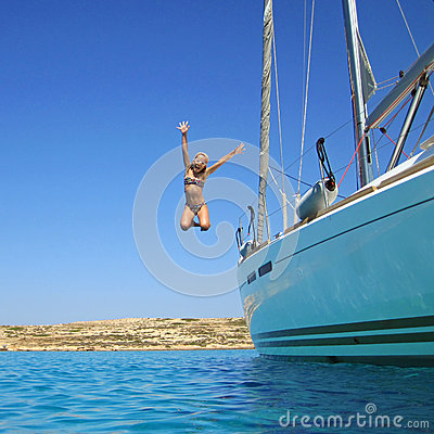 Girl jumping in sea off boat