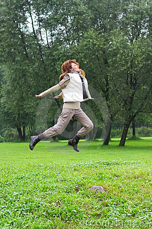 The girl jumps on a grass