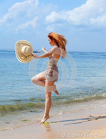 The girl jumps on an ocean coast.Portrait