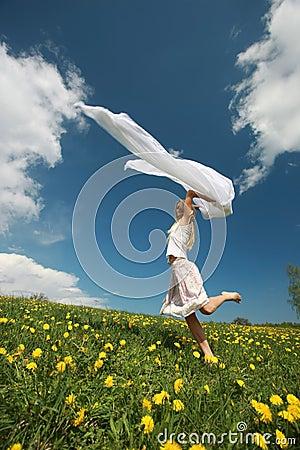 Free Girl Jumps Over Dandelion Field Stock Photo - 5532710