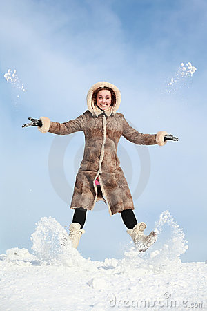 Girl jumps and throw snow hands and feet
