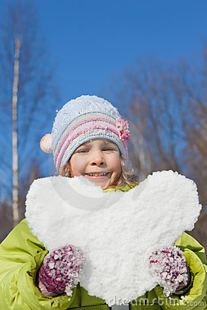 Girl keeps in hands hearts from snow
