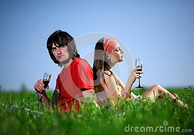 Girl in kerchief and boy with wineglasses on grass