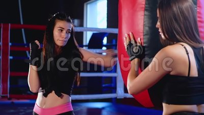 Close Up Cute Young Brunette Woman Athlete Fulfills Blows On Punching Bag Working With His Hands In Black Sports Bandages