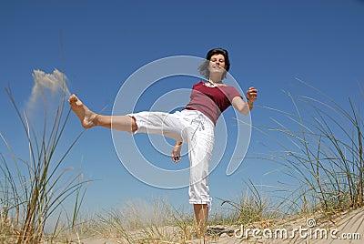 Girl kicking sand