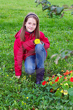 Girl kid posing with a flower in a meadow