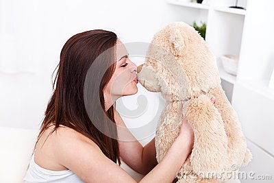 Girl kissing her teddy bear