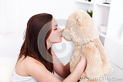 Girl kissing her teddy bear