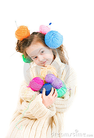 Girl with knitting spokes and balls of threads in hair