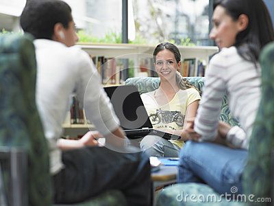 Girl With Laptop Looking At Friends In Library