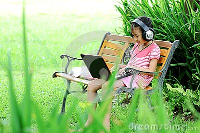 Girl with a laptop in the park grass