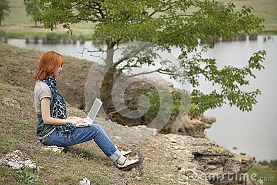 Girl with laptop at rock near lake and tree.
