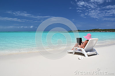 Girl with a laptop on the tropical beach