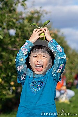 Girl Laughing and Balancing an Apple
