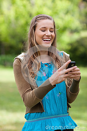 Girl laughing while reading a text on her phone