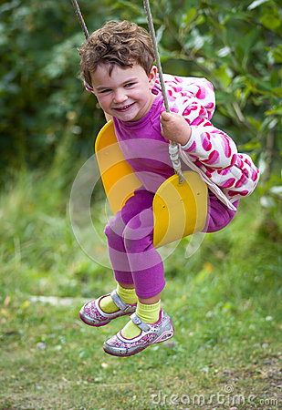 Girl laughing on swing