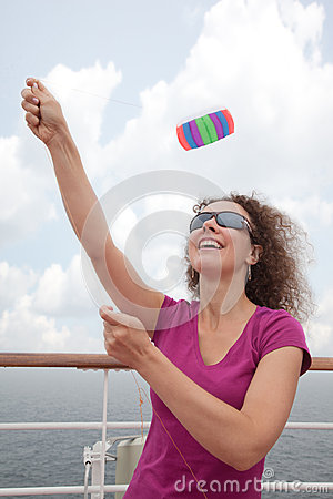 Girl launch kite from deck of ship