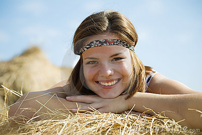 Girl laying on straw bail