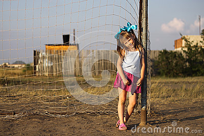 Girl lean on football gate.