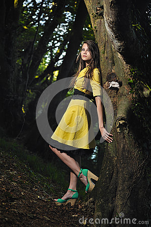 A girl leaning against a tree.