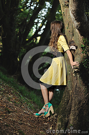 A girl leaning against a tree in a forest.