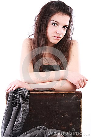 Girl leaning on old suitcase
