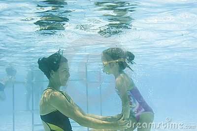 Girl learning to swim with mom