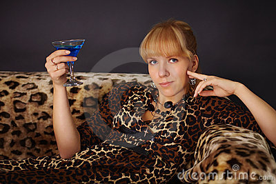 Girl in leopard dress, drinking a blue cocktail