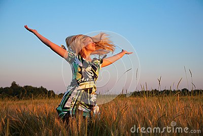 Girl with lifted hands and flying hair on wheaten