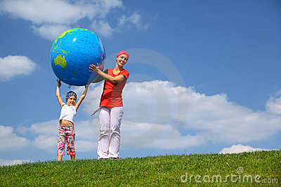 Girl lifts an globe upwards and mother helps