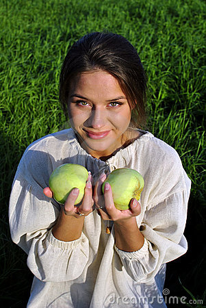 Girl in a linen shirt, holding apples