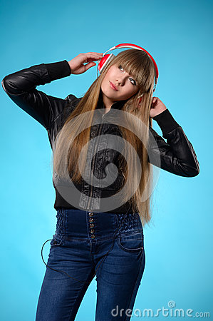 Girl listening to music with big red headphones