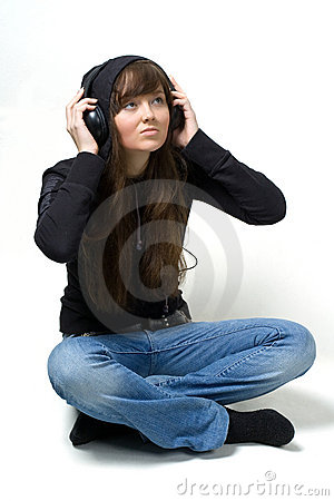 The girl listening to music through ear-phones