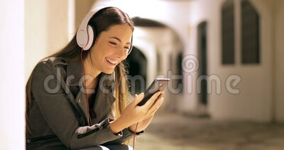 Girl listening to music from smart phone in the night. Happy girl listening to music from smart phone sitting in the street in the night stock video