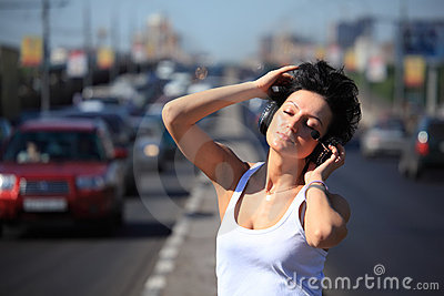 Girl listens music in ear-phones on highway middle