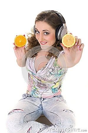 Girl listens music and eats orange