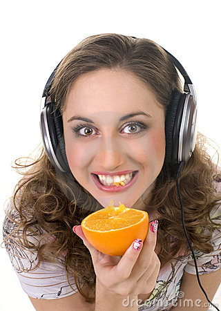 Girl listens music and eats orange