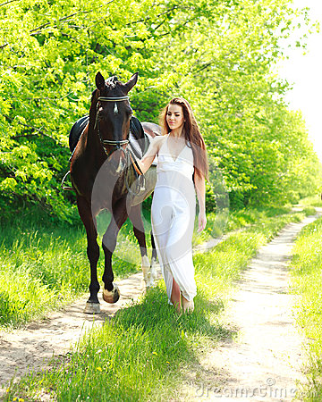 A girl in a long white dress with a horse goes on a country road