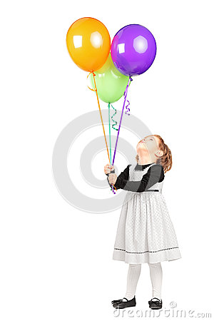 Girl looking at bunch of balloons
