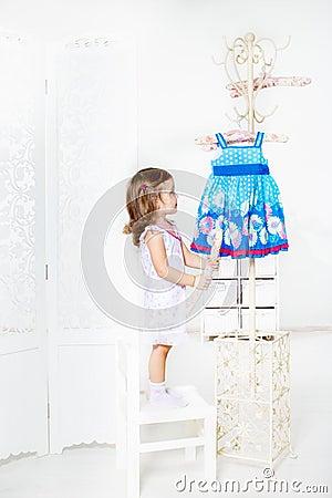 Girl looking on the coat rack