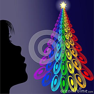 Girl looking colorful christmas tree