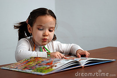 Girl looking in a colorful story book