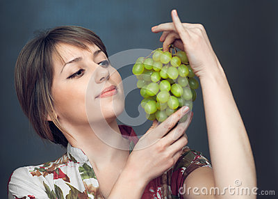 The girl is looking on grapes